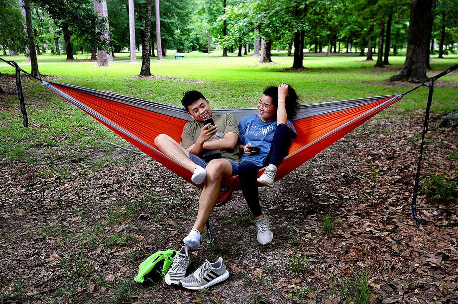 Tri Nguyen and Kathy Tran enjoy a peaceful evening on a hammock strung beneath the tall trees in Wuthering Heights Park Tuesday. Nguyen says the park is one of his favorite places where he and high school friends often spent time together. Though his classes at Lamar now cut into his free time, he still enjoys coming out to spend time several times a year. Photo taken Tuesday, June 4, 2019 Kim Brent/The Enterprise Photo: Kim Brent / The Enterprise / BEN
