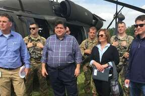 """Local and state leaders gather with members of the Illinois National Guard in Grafton, Illinois, to take a helicopter tour of Mississippi River floodwaters on June 4, 2019. Front row from left: John Sullivan, Gov. JB Pritzker, Sen. Rachelle Crowe (D-Glen Carbon), Sen. Steve McClure (R-Jacksonville). Back row from left: members of the Illinois National Guard. Photo courtesy of Illinois Senate Democrats. """"It was motivating to see each community come together to manage the rising flood waters,"""" Crowe said. """"I wanted to commend the first responders and volunteers that are working tirelessly to protect their homes, businesses and citizens. IEMA has also done a tremendous job organizing their efforts with the National Guard to keep state resources available for those who are struggling."""""""