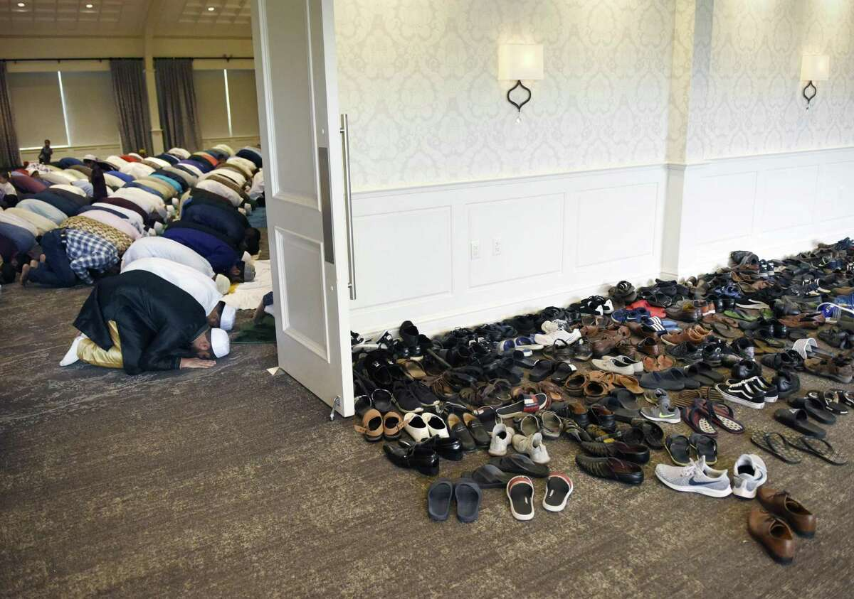 Hundreds of shoes sit outside the hall entrance as Muslims bow in prayer during the Stamford Islamic Center's Eid al-Fitr celebration at the Stamford Italian Center in Stamford, Conn. Wednesday, June 5, 2019. The ceremony celebrated the breaking of the fast for the month of Ramadan with Salaah prayers, charity giving, and gifts for children.