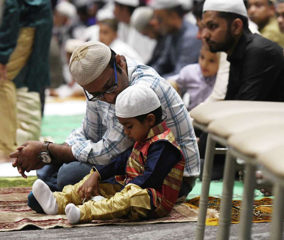 Stamford's Inayath Khan and his son Saffan Khan, 2, attend the Stamford Islamic Center's Eid al-Fitr celebration at the Stamford Italian Center in Stamford, Conn. Wednesday, June 5, 2019. The ceremony celebrated the breaking of the fast for the month of Ramadan with Salaah prayers, charity giving, and gifts for children.
