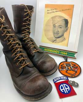 A photo of Private First Class Leon Yee, the author's uncle, along with Yee's boots and insignia from his service as a D-Day paratrooper during World War Two.