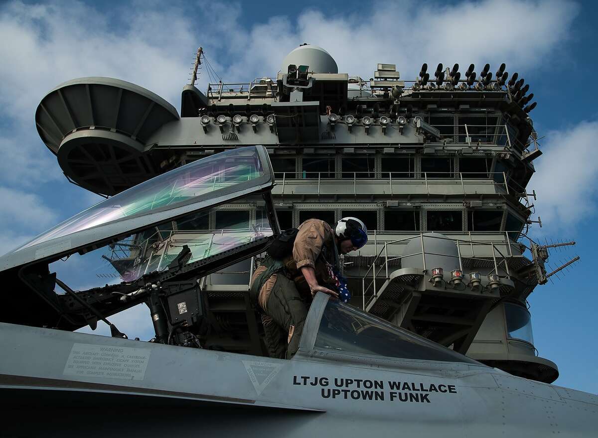 A pilot gets in the cockpit of an F/A-18 fighter jet on the deck of the USS Abraham Lincoln aircraft carrier in the Arabian Sea, Monday, June 3, 2019. The U.S. aircraft carrier the White House ordered to the Mideast over a perceived threat from Iran remains outside of the Persian Gulf amid efforts to de-escalate tensions between Tehran and Washington. (AP Photo/Jon Gambrell)