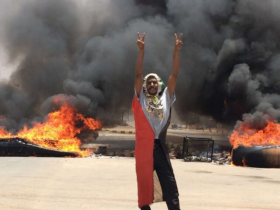 A protester flashes the victory sign in front of burning tires and debris near Khartoum's army headquarters. Opposition leaders say there will be no talks as long as the violence continues. Photo: Associated Press