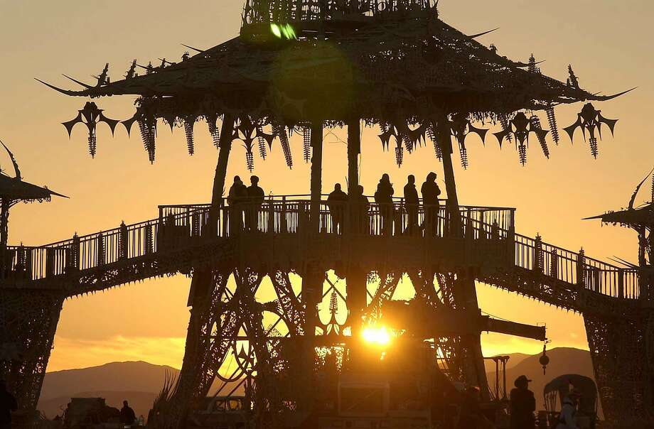 People gather to watch the sun rise from the Temple of the Stars at the Burning Man counter culture arts festival in the Black Rock Desert, north of Reno, Nev., Friday, Sept 3, 2004. (AP Photo/Reno Gazette-Journal, Scott Sady) Photo: Scott Sady, AP