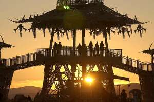 People gather to watch the sun rise from the Temple of the Stars at the Burning Man counter culture arts festival in the Black Rock Desert, north of Reno, Nev., Friday, Sept 3, 2004. (AP Photo/Reno Gazette-Journal, Scott Sady)