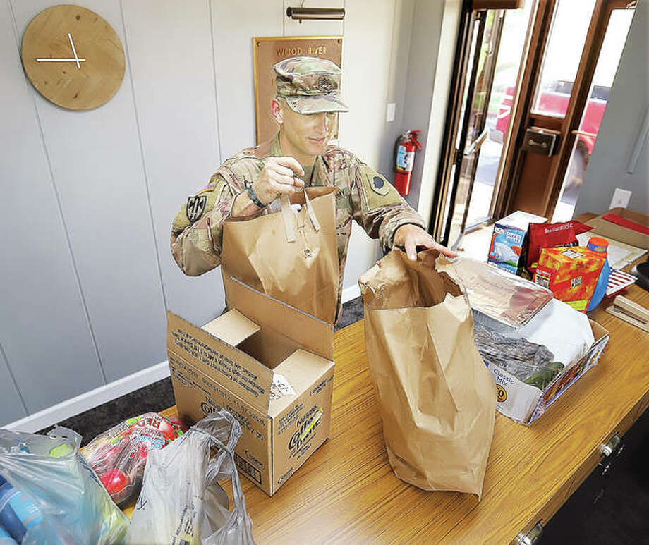 Illinois National Guard Staff Sgt. Josh Griffen picks up lunch for himself and his men Wednesday at the offices of the Wood River Levee District. Riverbend Family Ministries in Wood River has been coordinating to collect food for the guard troops who are patroling the length of the levee to protect it from damage and sightseers.