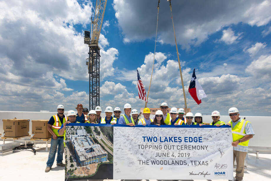 Team members from The Howard Hughes Corp.; architect, Preston Partnership; and construction manager, Hoar Construction celebrated the topping out of Two Lakes Edge in Hughes Landing on the roof of the eight-story luxury, multifamily development. Photo: The Howard Hughes Corp.