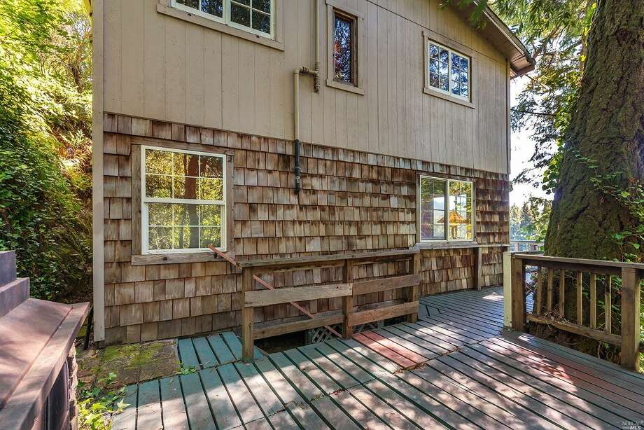 A 1930 redwood cabin nestled on a hillside at 14800 River Rd. in Guerneville is listed for $99,000. Photo: 14800 River Rd, Guerneville