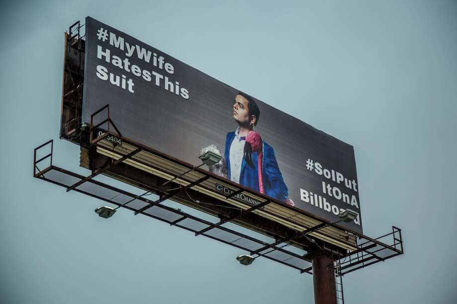 """Hanging over a stretch of Loop 410, near Cowboys Dancehall, are two photos of Chris Marti modeling his favorite new, blue plaid suit he feels his best in, but his wife, Meredith, hates. """"#MyWifeHatesThisSuit"""" and """"#SoIPutItOnABillboard,"""" join Chris on the photos, along with a few quirky props like two furry plush animals, a garden flamingo and a bouquet of artificial flowers. Photo: Courtesy, Marti Family"""