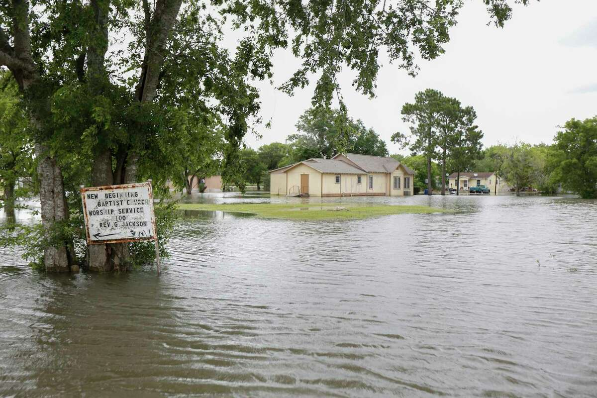A sign welcoming worshipers to New Beginning Baptist Church is surrounded by flood water Wednesday, June 5, 2019, in Kendleton.