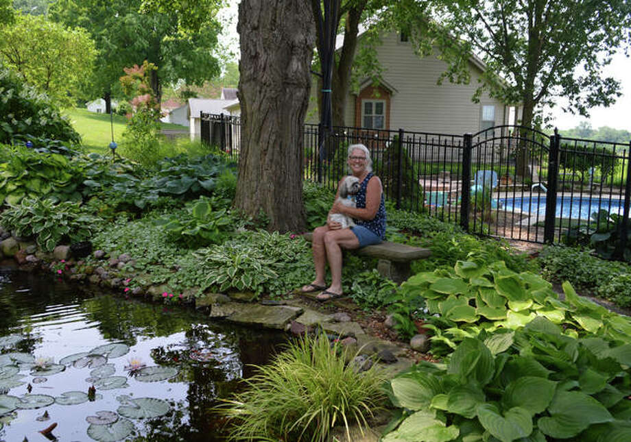Debbie Rathert and her Shih Tzu, Rocky, enjoy taking a rest on a pondside bench Photo: Vicki Bennington | For The Telegraph