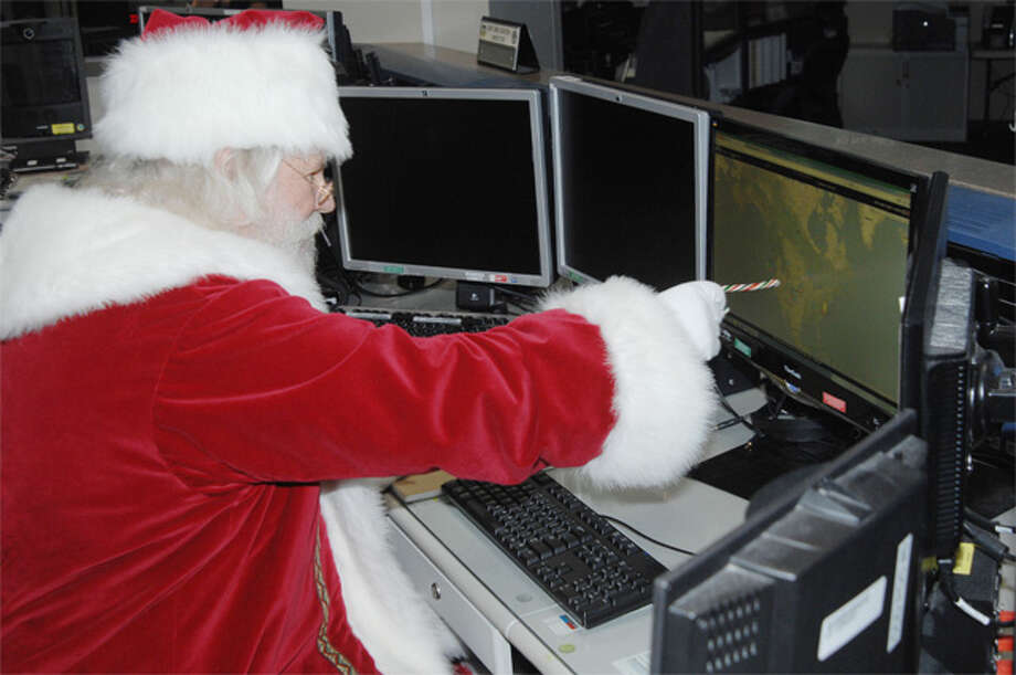 In Septmber, Santa Claus reviews his flight plan for his Dec. 25 trek across the globe in the North American Aerospace Defense Command and U.S. Northern Command Current Operations Center at Peterson Air Force in Colorado Springs, Colo.