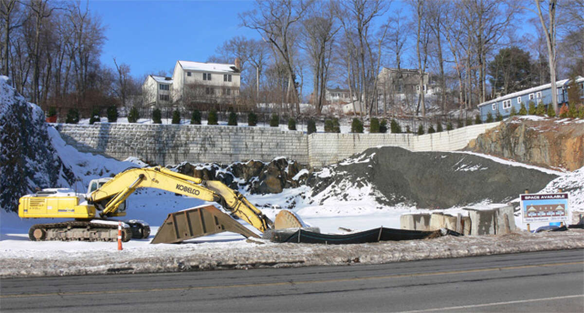 Ledge is being excavated and retaining walls added to create a site for a retail building and parking lot on this 1.1-acre lot across the street from the Sports Center of Connecticut.