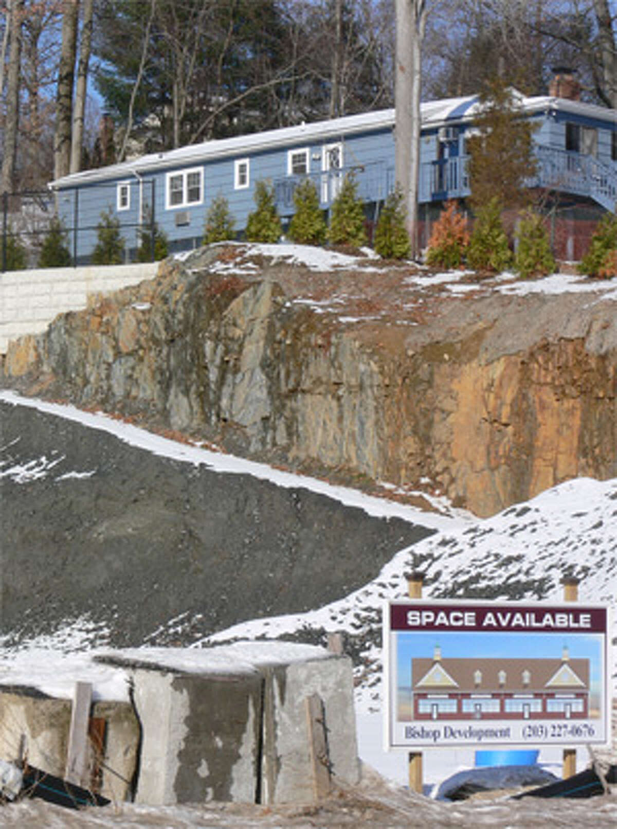 A view of the ledge's vertical drop from the Turner Road house to the Route 110 road level, where a retail building and parking lot will be built.