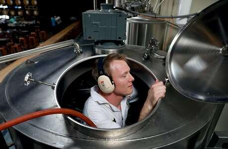 Pilot brewer Dane Volek cleans a brew kettle at Anchor Public Taps. Photo: Yalonda M. James / The Chronicle