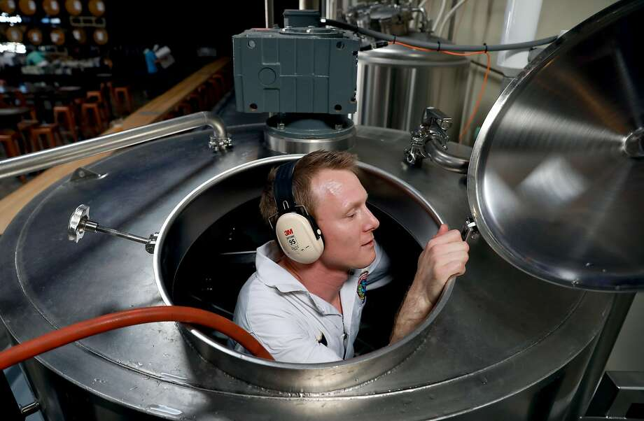 Pilot brewer Dane Volek cleans a brew kettle at Anchor Public Taps. Photo: Yalonda M. James / The Chronicle