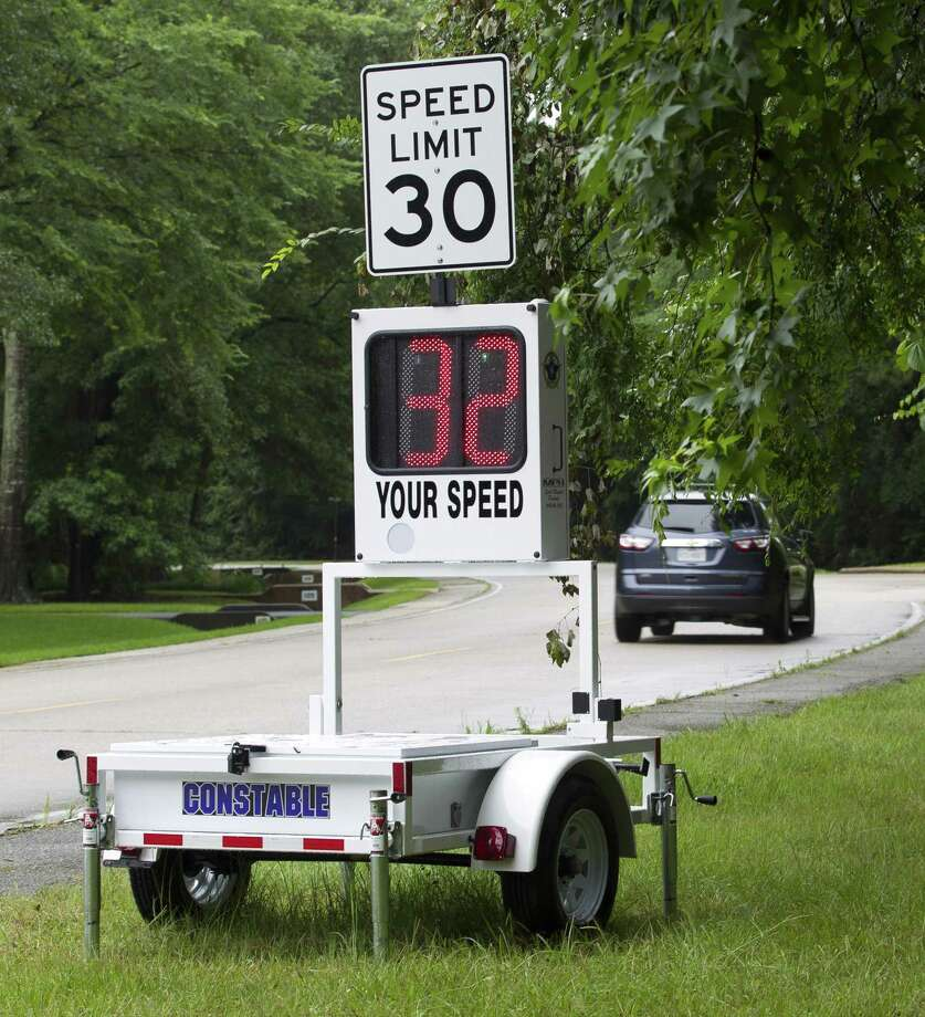 Motorists on Grogan's Point Road pass by a new speed trailer deployed by Montgomery County Precinct 3 Constable's Office in the Grogan's Mill subdivision, Wednesday, June 5, 2019, in The Woodlands. The new trailer, awarded through a nearly $10,000 grant by Texas Governor Greg Abbott's office, shows drivers how fast they are going as a speed deterrent. Photo: Jason Fochtman, Houston Chronicle / Staff Photographer / Houston Chronicle