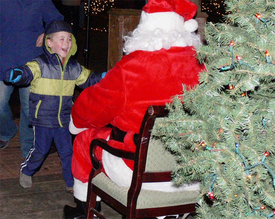 A youngster runs toward Santa Claus at the Huntington Green tree-lighting ceremony.