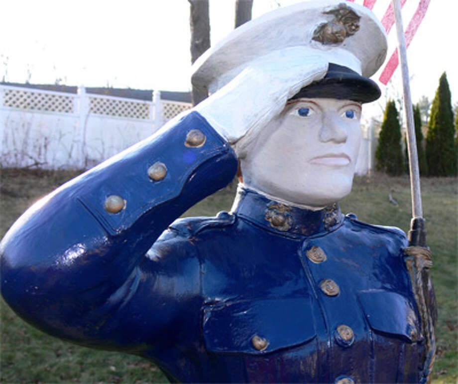 Leroy Glover, who served in the Marines during World War II, proudly displays this painted Marine statue in his yard.