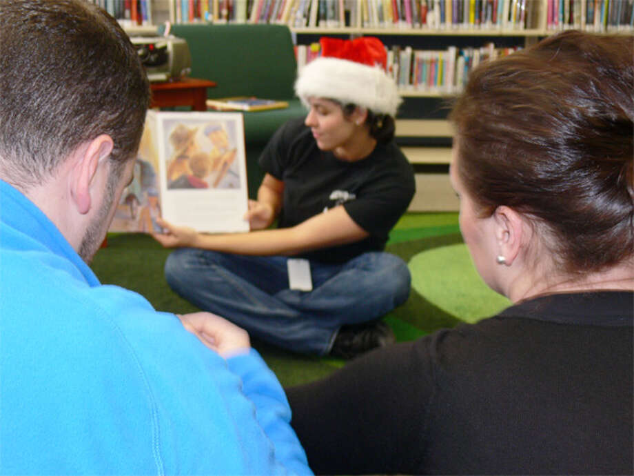 Desiree Caproaso of the Echo Hose Hook & Ladder Company reads a book during story time at Meet Santa Day.