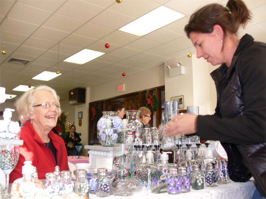 Debra McGlone, right, of Shelton looks at painted glass items being sold by crafter Sandy Beauton of Derby at the fair.