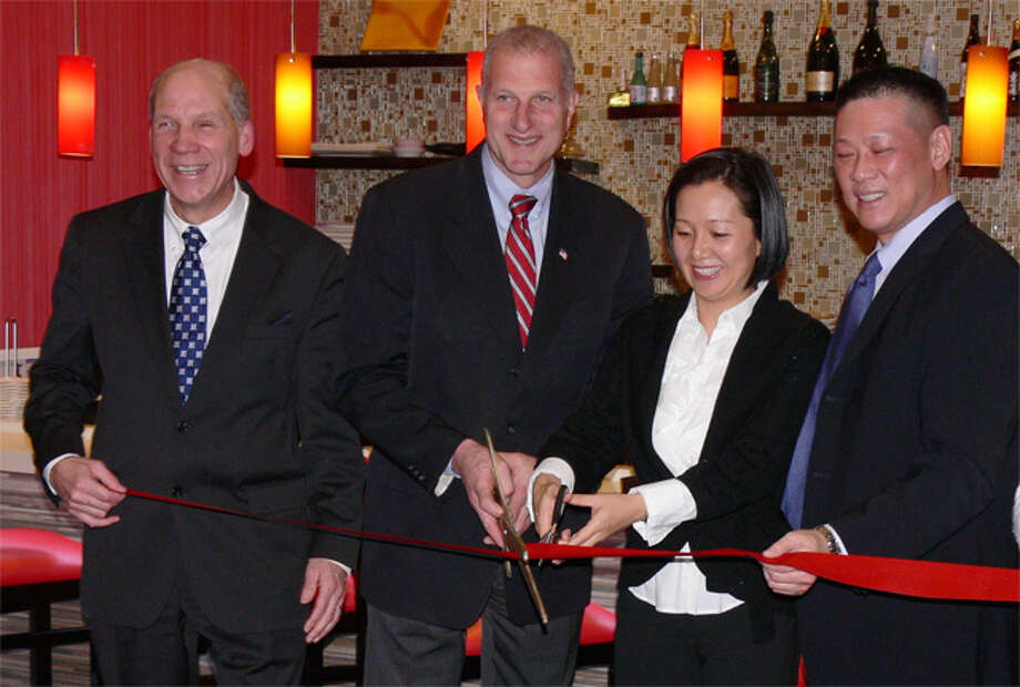 At the Red Lotus restaurant ribbon-cutting ceremony on Monday are, from left, Greater Valley Chamber of Commerce President Bill Purcell, Mayor Mark Lauretti, and owners Nia Chen and Larry Wang.