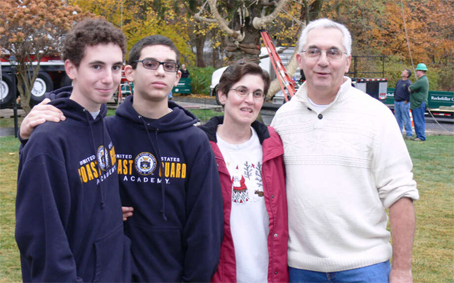The Vargoshe family of Shelton — from left, son Nathan, 15; son Noah, 12; mother Louise, and father John — pose in front of the tree just before it was cut down to become the Rockefeller Center Christmas tree.