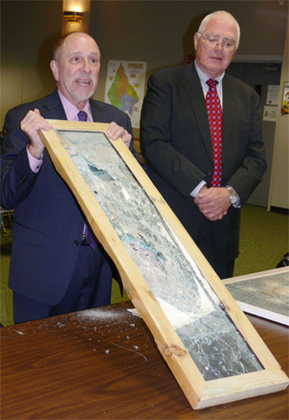 School Supt. Freeman Burr, left, shows a security film-coated window that withstood gun shots and other damage to the Board of Aldermen, with school Finance Director Al Cameron at his side.
