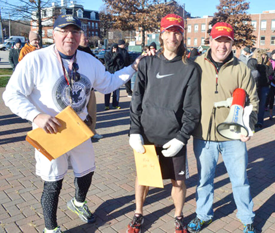 Runner Tim Milenkevich, center, receives his first place award from Commodore Hull Road Race directors Glenn Gaetano, left, and Tom Wilson.