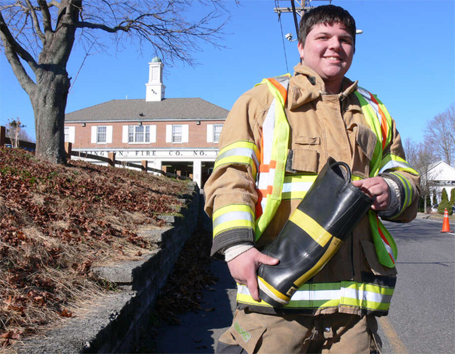 Allen Goodman of the Huntington Volunteer Fire Company, with the fire station in the background, prepares to accept donations from motorists during the Saturday boot drive.