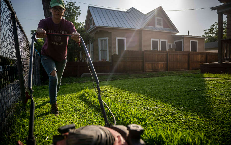 Patricia Pietro cuts the grass in one of the rentals she manages for an independent investor on West Euclid Avenue in San Antonio. Pietro lives in the back of this property with her boyfriend and their infant son. Photo: Carlos Javier Sanchez