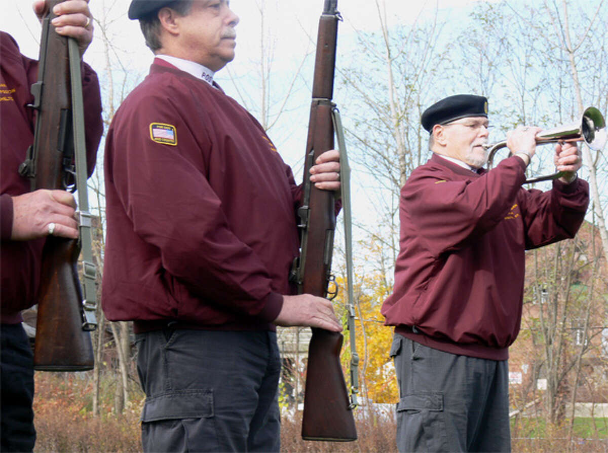 Ron Dietman, far right, of the local American Legion post's honor guard performs Taps during the 2013 Shelton Veterans Day ceremony.