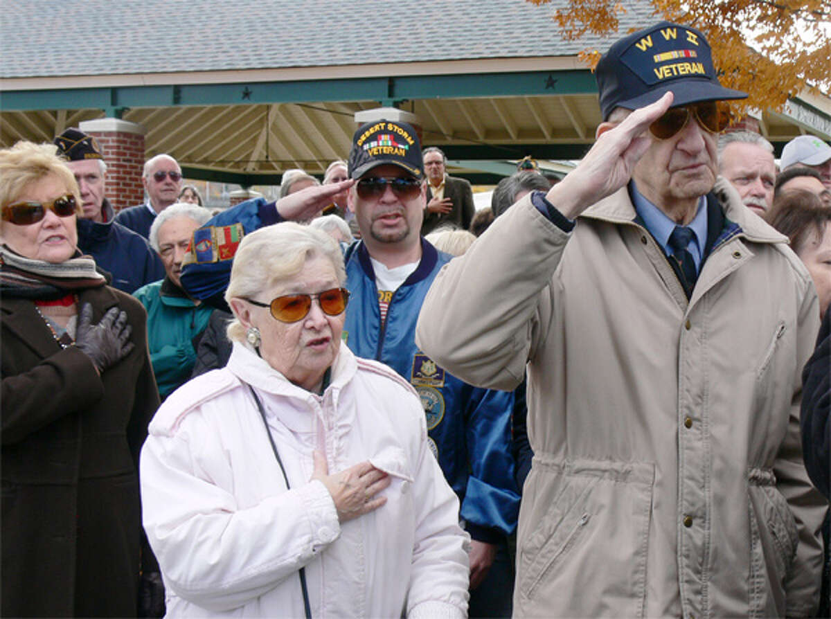 People in the crowd salute and stand at attention during the 2013 Shelton Veterans Day ceremony.