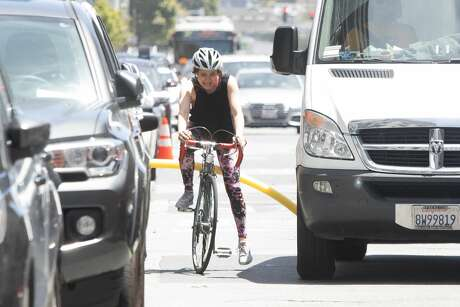 With a pool noodle attached to the bicycle of SFGATE Producer Michelle Robertson has difficulty maneuvering between park cars and a van in downtown San Francisco. Photo: Douglas Zimmerman/SFGate.com