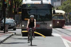 A Muni bus is unable to get around SFGATE Producer Michelle Robertson and her attached pool noodle on Market Street in San Francisco.