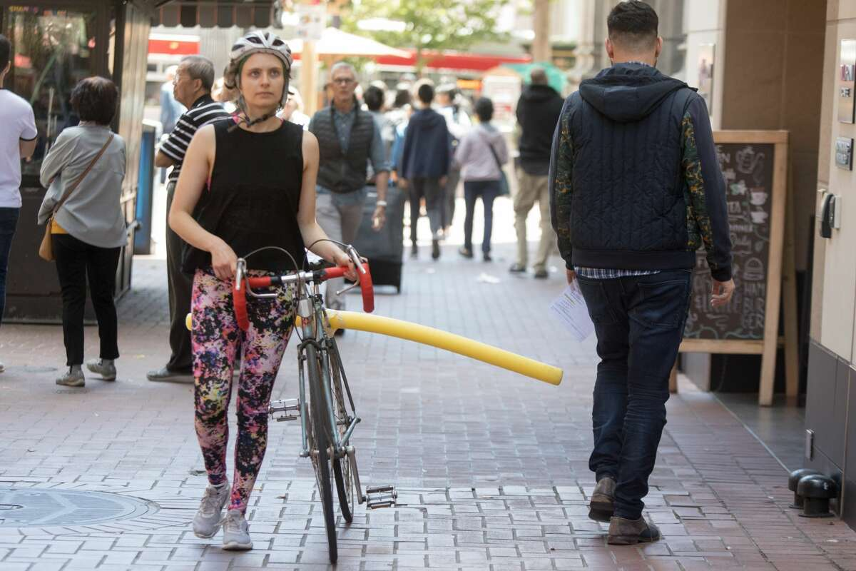 A pedestrian ducks a pool noodle attached to SFGATE Producer Michelle Robertson?•s bicycle on the sidewalk on San Francisco.