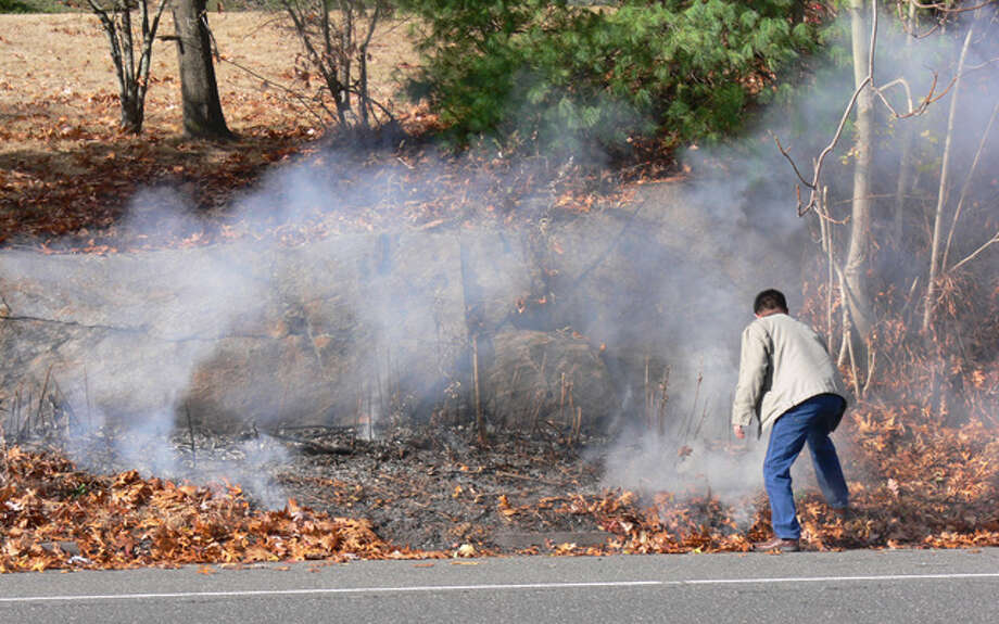 A driver passing by the small brush fire in Shelton got out of his vehicle to help put the small roadside blaze out.