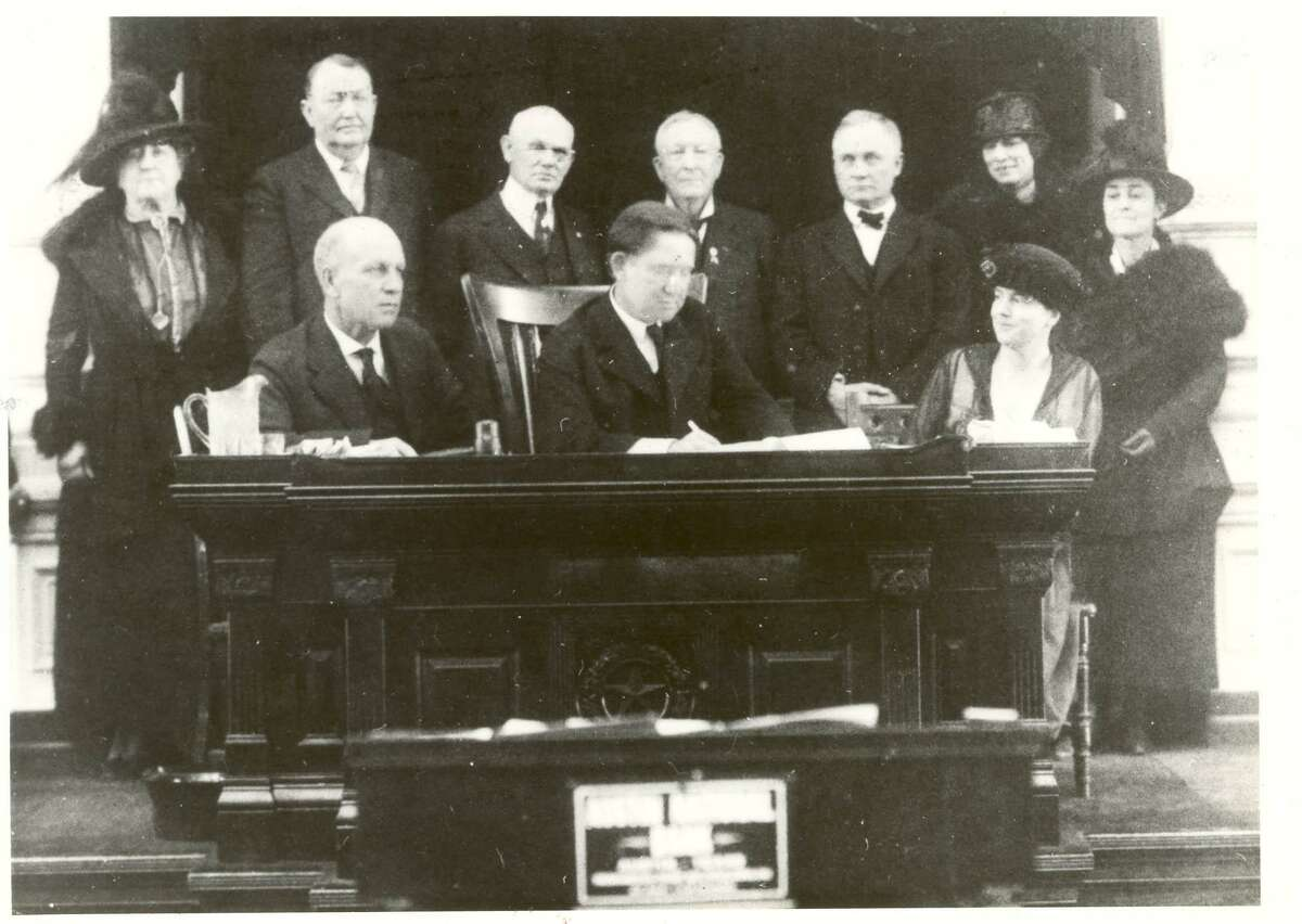 Texas Gov. William P. Hobby signs the Texas Woman Suffrage Resolution in a ceremony in the Texas Senate on Feb. 5, 1919. Minnie Fisher Cunningham, Texas senate leaders and other sponsors of the suffrage movement look on.