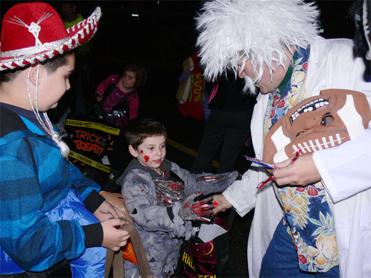 At the 2013 Trick or Trunk in Shelton, brothers Justin, 10, left, and Michael Shae, 4, get candy from Michael Pierce, who is dressed like a mad scientist.