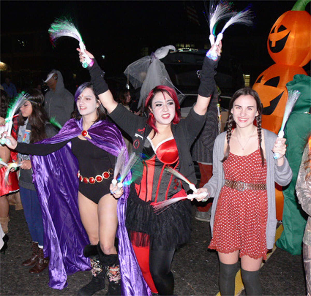 A group of girls dance to the deejay music in their costumes at the trick-or-trunk event.
