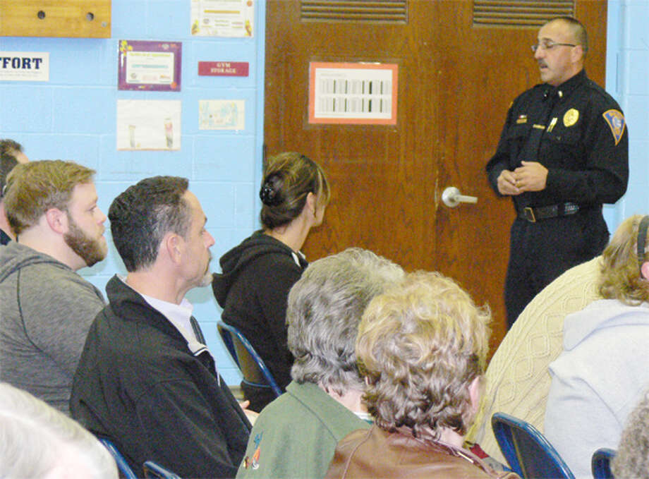 Shelton Police Sgt. George Rodrigues talks to residents about crime prevention during a neighborhood meeting at Long Hill School.
