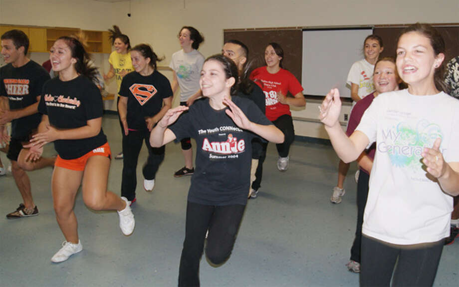 """In foreground, from left, Shelton High School senior Ariana Maione, Woodland High senior Hannah Reis, Shelton High junior Elise Sullivan with other """"Sing!"""" cast members."""