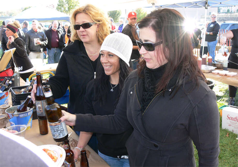 From left, the Dew Drop Inn's Barbara Chernesky of Shelton, Kenna Carlucci of Derby and Kelly Kane of Naugatuck pour beers for guests. Kenna and her husband, Jason Carlucci, own the Dew Drop Inn.