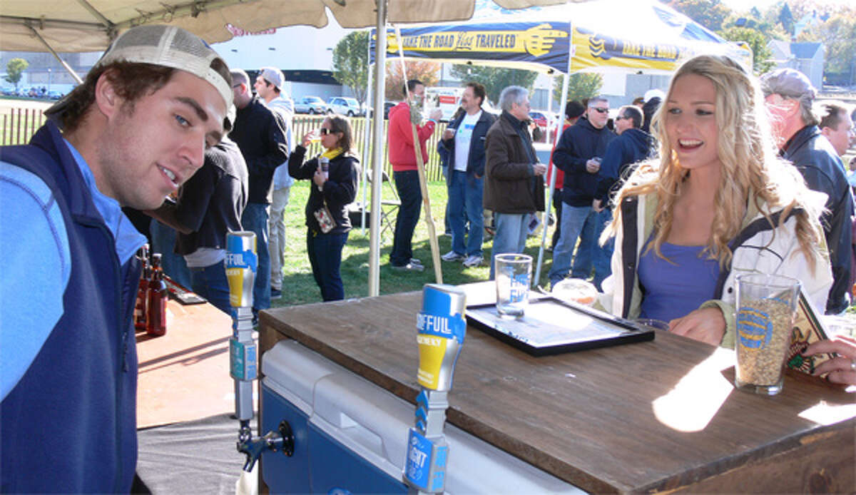 Marissa Labelle, far right, waits for Ben Hoeft from Half Full Brewery in Stamford to fill up her cup at Hoptoberfest 2013.