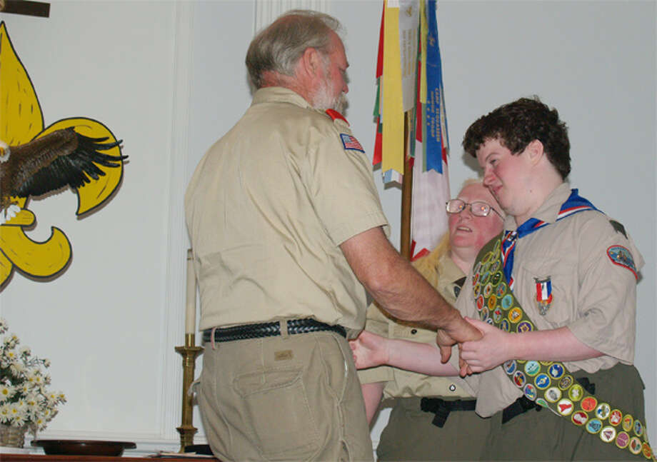 Joshua Sussan, right, of Shelton receives congratulations from Scoutmaster Mark Krom of Troop 1 during his Eagle Scout ceremony.