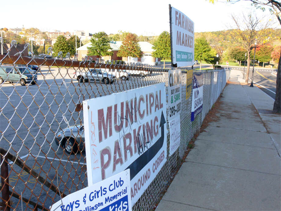 A view of the chain-link fence around the municipal parking lot that will be replaced by a safer, more decorative fence. The Farmers Market Building is in the background.