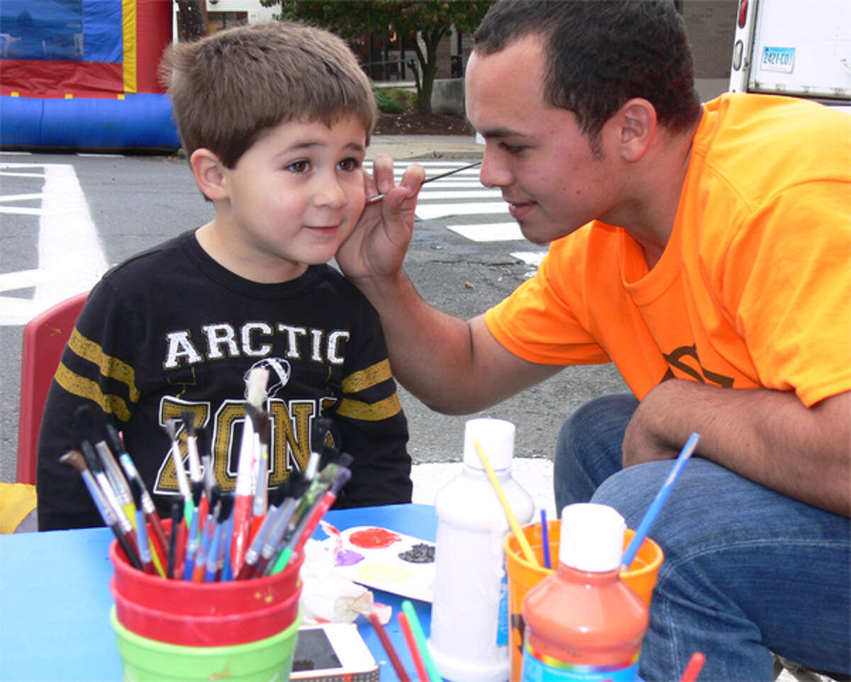 Alex Obied of Shelton has a balloon painted on his face by Bryan Chervony of the Boys & Girls Club during Shelton Day 2013.