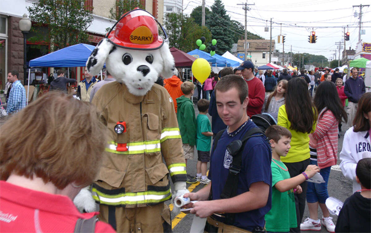 Shelton firefighters are joined by mascot Sparky while distributing fire safety information to youngsters during Shelton Day.