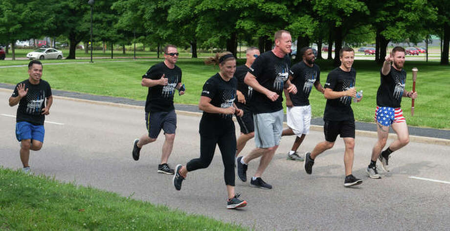 Breezing along in the Law Enforcement Torch Run are (L-R): Patrol Officer Xac Vo, Detective Phillip Ragsdale, Detective Trisha Bland, Lt. Adam Severit, Sgt. John Wayne, Patrol Officer Kasey Hoyd, Patrol Officer Anthony Hettinger and Patrol Officer Jeff Wooldridge. Photo: For The Intelligencer