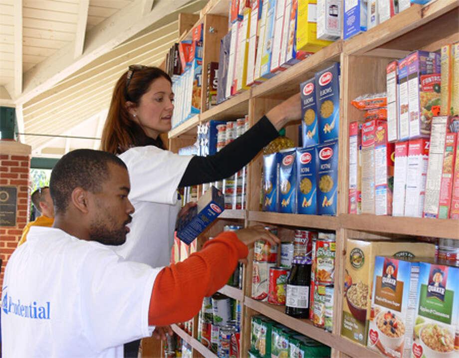 Shanar Fraiser, left, and Carolyn Cargnel, both of Shelton, put items on the shelves at Harvest House on Saturday morning.